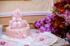 Pastel de bodas rosado en una tabla Foto de archivo