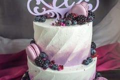 Pastel de bodas tres-con gradas delicioso hermoso adornado con las bayas arándano y zarzamoras en color púrpura rosado Imagenes de archivo