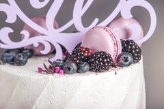 Pastel de bodas tres-con gradas delicioso hermoso adornado con las bayas arándano y zarzamoras en color púrpura rosado Foto de archivo