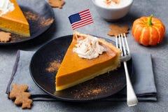 Pastel de calabaza, tarta hecha para el día de la acción de gracias con crema azotada con la bandera americana en el top Imagen de archivo