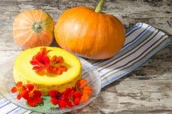 Pastel de queso adornado con las flores frescas y la calabaza Imágenes de archivo libres de regalías