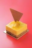 Pastel de queso amarillo en fondo rojo Imagenes de archivo