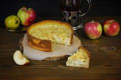 Pastel de queso de Apple en una cocina rústica con una caldera de té en el fondo oscuro de madera imagen de archivo libre de regalías