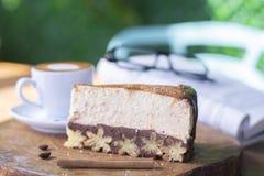 Pastel de queso de Churros y café del macchiato con el fondo del libro y de los vidrios imagenes de archivo
