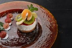 Pastel de queso con las frutas y la crema Postre En una superficie de madera imagen de archivo