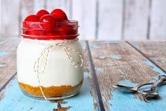 Pastel de queso de la cereza en un tarro de albañil en la madera rústica Imagen de archivo libre de regalías