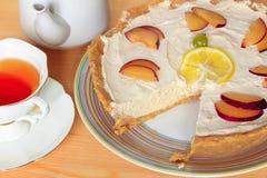 Pastel de queso de la fruta con té Fotos de archivo