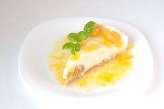Pastel de queso de la vainilla con el melocotón y la salsa dulce imágenes de archivo libres de regalías
