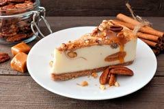 Pastel de queso del caramelo de la pacana con un fondo de madera Imágenes de archivo libres de regalías