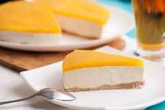 Pastel de queso del mango en la placa blanca con la cuchara Foto de archivo libre de regalías