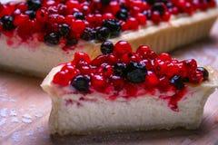 Pastel de queso del postre con los redberries y los arándanos en polvo del tablero de madera y del azúcar Foto de archivo libre de regalías