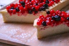 Pastel de queso del postre con los redberries y los arándanos en polvo del tablero de madera y del azúcar Ciérrese encima de la v Imágenes de archivo libres de regalías