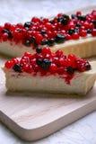 Pastel de queso del postre con los redberries y los arándanos en polvo del tablero de madera y del azúcar Cierre para arriba Fotos de archivo