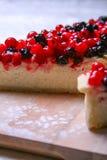 Pastel de queso del postre con los redberries y los arándanos en polvo del tablero de madera y del azúcar Cierre para arriba Visi Fotografía de archivo libre de regalías