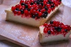 Pastel de queso del postre con los redberries y los arándanos en polvo del tablero de madera y del azúcar Visión superior Fotos de archivo libres de regalías