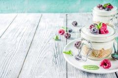 Pastel de queso en tarros repartidos con las bayas del verano fotos de archivo libres de regalías