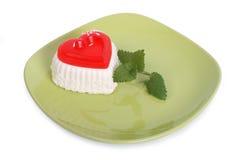 Pastel de queso en una forma del corazón con la menta en la placa verde Fotos de archivo