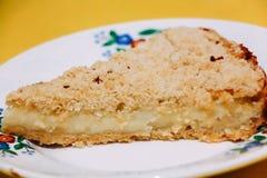 Pastel de queso en una placa en un fondo amarillo foto de archivo