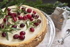 Pastel de queso festivo con las frambuesas, el romero y los lingonberries en el fondo de una rama del abeto y de una casa del jug fotos de archivo libres de regalías