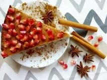 Pastel de queso hecho en casa con los palillos de la granada y de canela y las estrellas de los anis Imagen de archivo