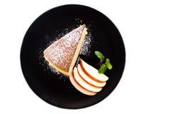 Pastel de queso japonés en la placa negra Servido con el desmoche de la formación de hielo y la manzana cortada Visión superior Imagenes de archivo