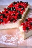 Pastel de queso de la empanada con las bayas en la placa de madera Imagen de archivo