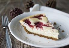 Pastel de queso de la frambuesa con el fondo festivo del invierno Foto de archivo libre de regalías