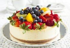 Pastel de queso rematado con las bayas y las frutas Foto de archivo