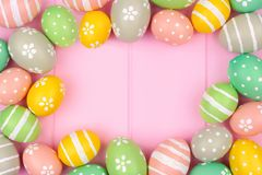 Pastel Easter egg frame against a pink wood background Stock Image