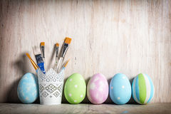 Pastel Easter eggs and brushes in a rustic cup Royalty Free Stock Image