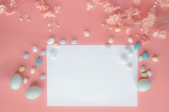 Pastel Easter Eggs Malt Candy Blank Card and Flowers over a Coral Colored Background. Pastel Easter eggs, malt candy covered chocolate eggs, and flower blossoms royalty free stock photos