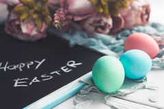 Pastel Easter eggs on white wooden board with chalkboard with Happy Easter inscription. And some flowers in the background Royalty Free Stock Photo