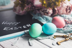 Pastel Easter eggs on white wooden board with chalkboard with Happy Easter inscription. And some flowers in the background Royalty Free Stock Photography