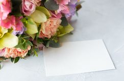 Pastel flowers bunch on a wooden background with empty tag. Copy Stock Image