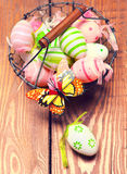 Pastel flowers, colorful Easter eggs in basket Stock Photography