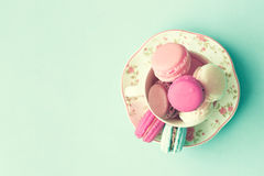 Pastel French Macarons. Pastel colored French macarons in a tea cup stock images