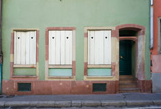 Pastel green and dark brown building with white windows and door Stock Images