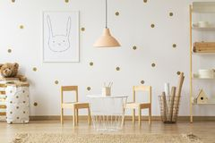 Pastel lamp above table between chairs in gold kid`s room interi. Or with poster. Real photo royalty free stock images