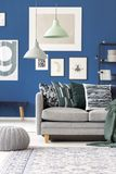 Pastel lamps above grey couch. With pillows against blue wall with gallery in living room with pouf stock image