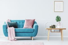 Pastel living room interior. Pink pillow on turquoise couch next to wooden table in pastel living room interior with poster royalty free stock photos