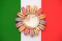 Pastel macarons around a coffee cup. Against of the flag of Italy Royalty Free Stock Image