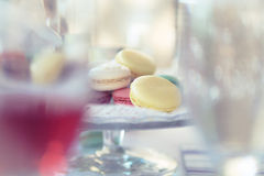Pastel Macarons on Cake Stands between glasses Stock Photos