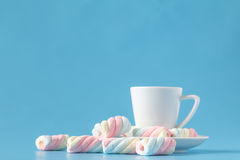 Pastel marshmallow and a white cup on a blue background. Sweet u. Nhealthy food Stock Images