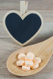 Pastel orange pills in wooden spoon with blank heart shape black Royalty Free Stock Photo