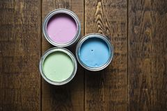 Pastel paint tins on wooden floorboards. Three cans of pastel shades in pink, blue and green, shot from above on floorboards stock photography