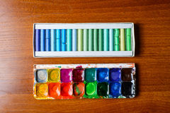Pastel pencils and watercolor paintbox Royalty Free Stock Photos