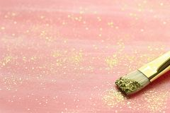 Pastel pink background with gold glitter and brush. Hand-painted pastel pink background with gold glitter and brush. Selective focus stock images