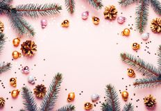 Pastel Pink Christmas Background. Festive frame of fir branches, golden balls and confetti.  stock photos