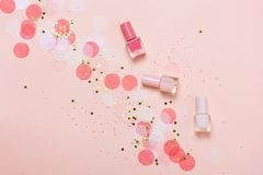 Pastel pink nail polishes and confetti, stars and sparkles. Bright and festive background. Manicure concept. Top view, flat lay royalty free stock photo