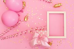 Pastel pink table with colorful balloons and confetti for birthday top view. Flat lay style royalty free stock photo